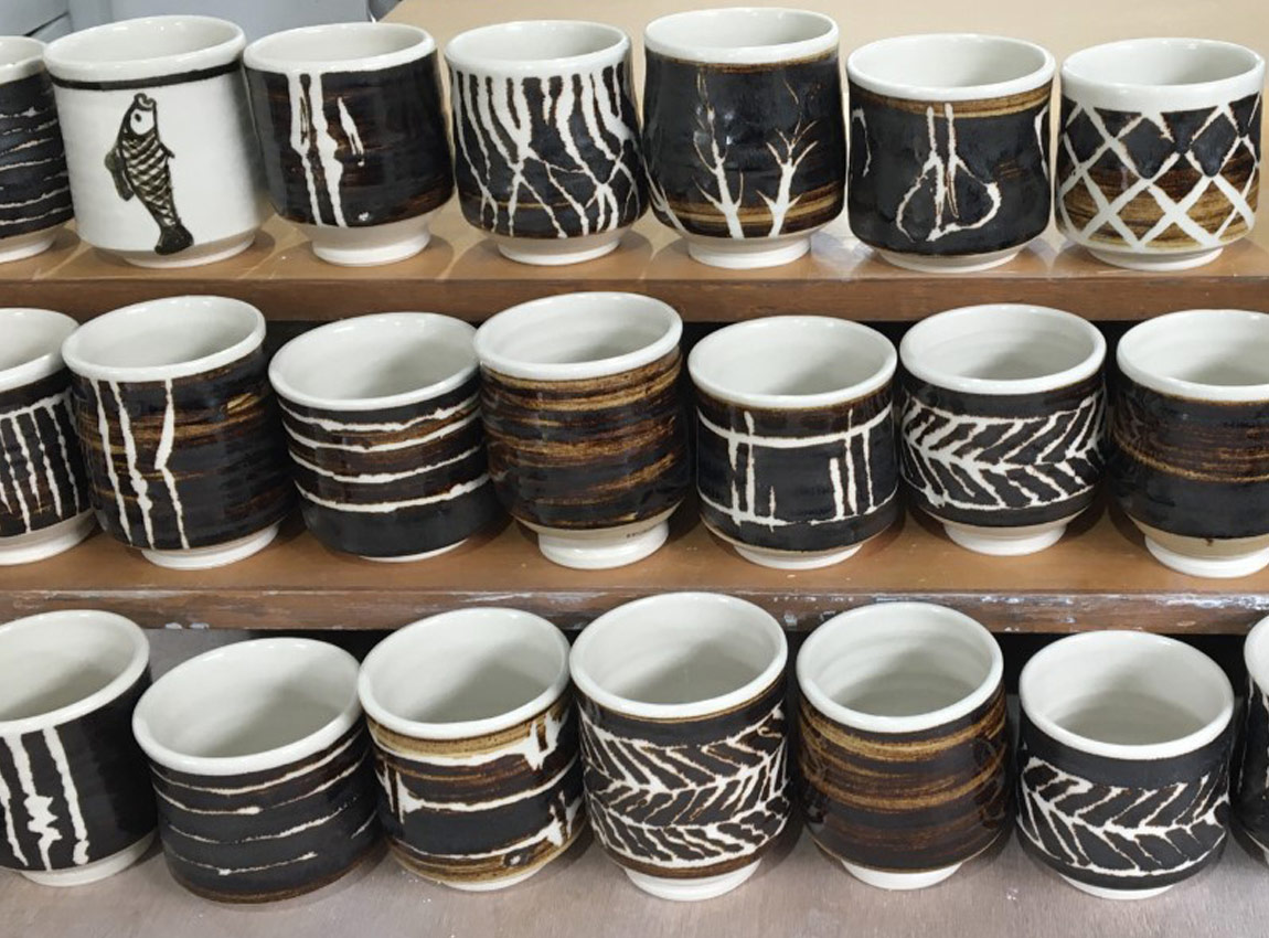 Ceramic teacups in a row by Gary McPhedran